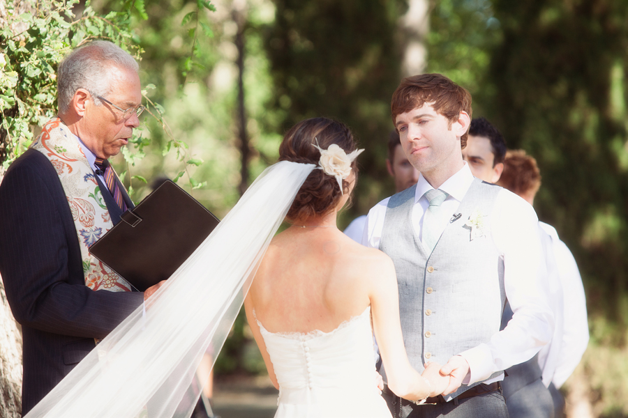 Groom saying vows to bride at outdoor winery wedding