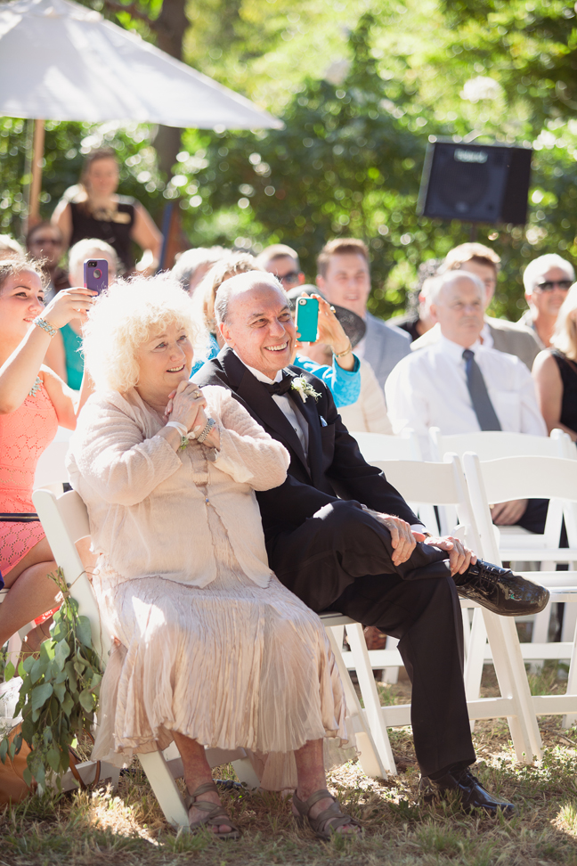 Parents of bride smiling during ceremony at outdoor wedding