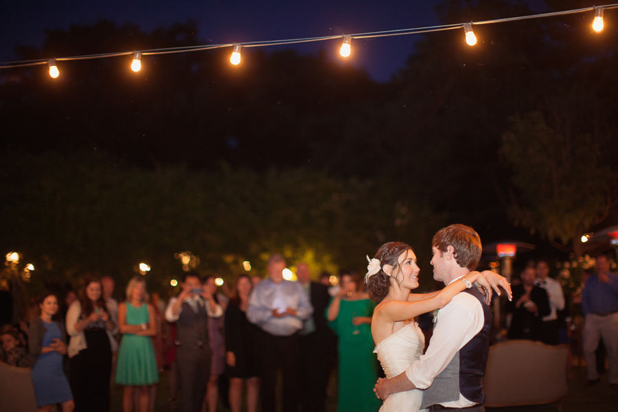 first dance under string of lights at outdoor wedding