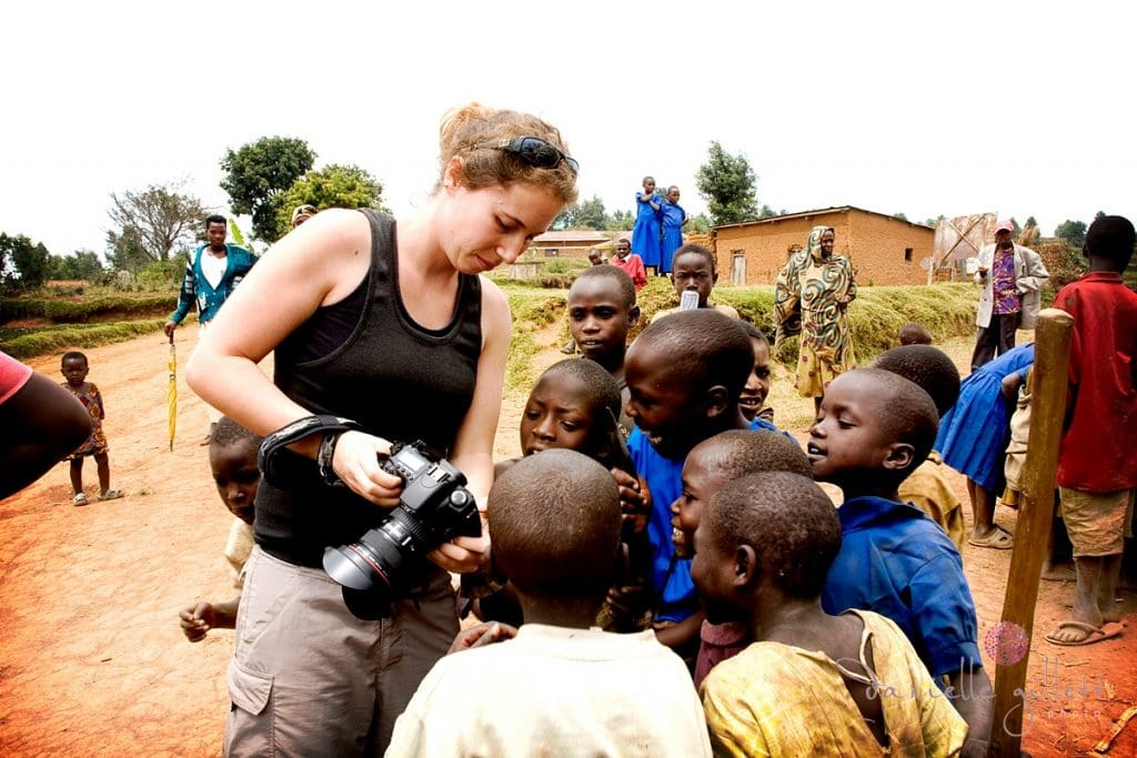 Photographer showing pictures to African village kids for charity project