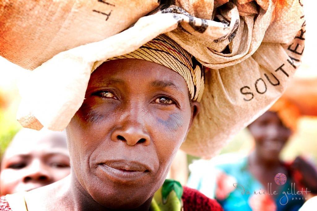 Rwandan carrying bag on head.