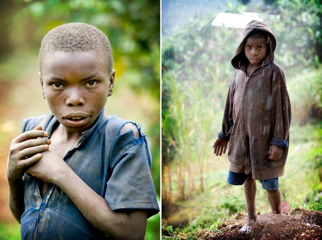 African Boy standing in rain. Rwandan on Bike. Picture for Project Rwanda Charity