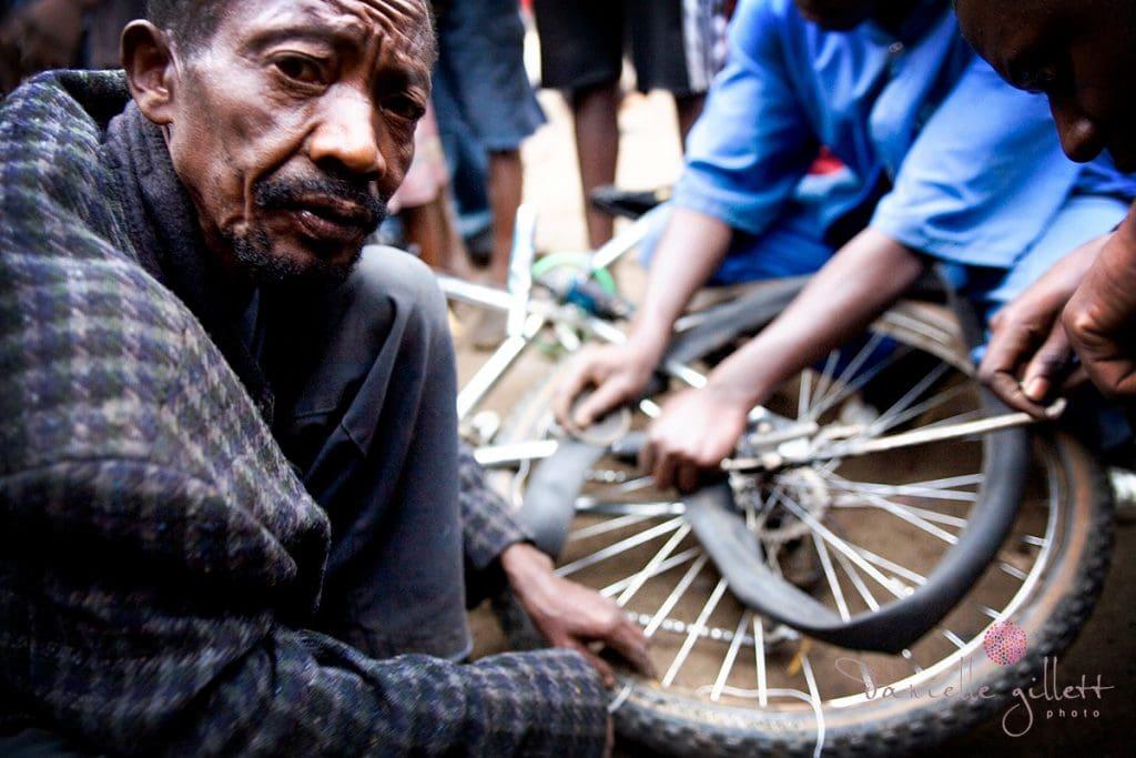 Man hand stitching the sidewall of the bike tire Rwanda Charity