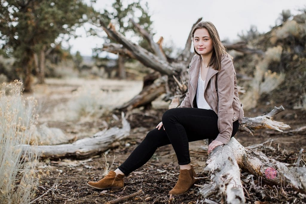 Senior Picture in Bend Oregon of girl sitting on fallen tree