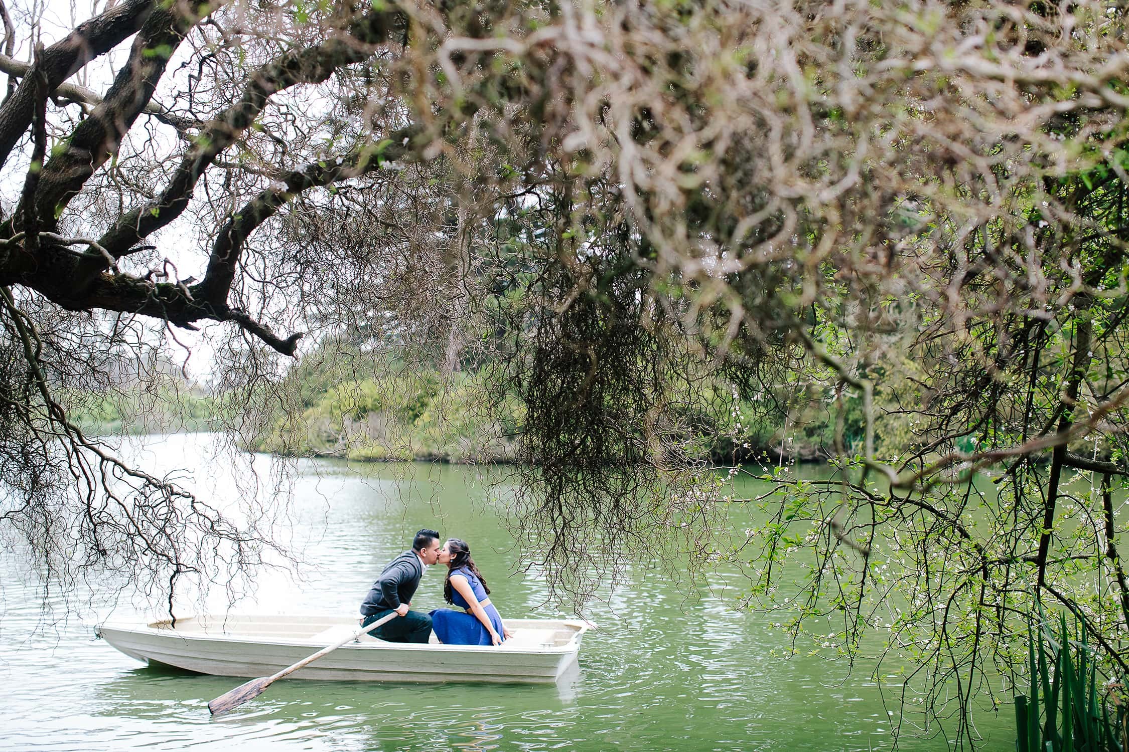 Engaged couple kissing in a boat in a lake at Golden Gate Park San Francisco