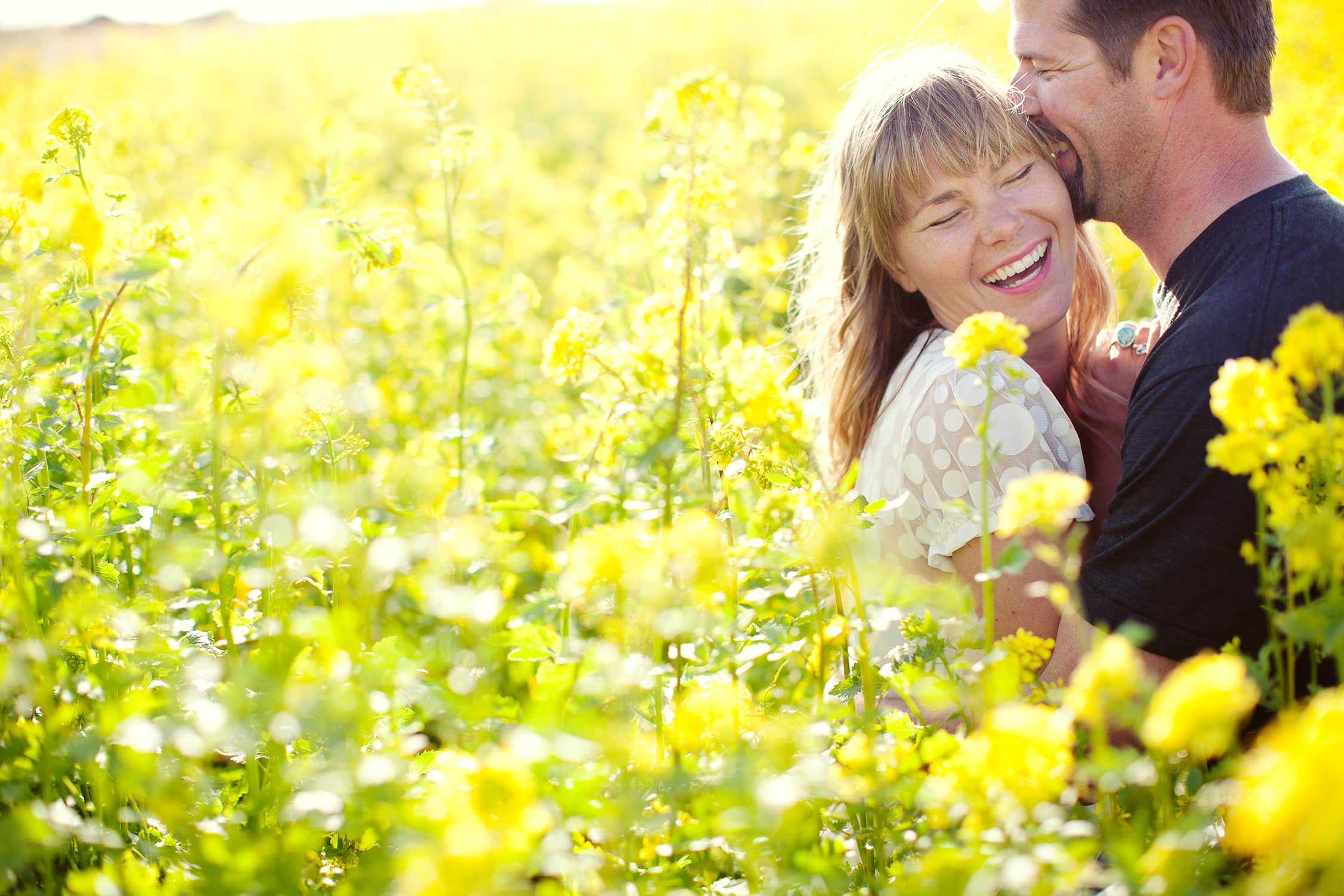 groom kissing bride on the cheek in a field of wildflowers in Santa Cruz California