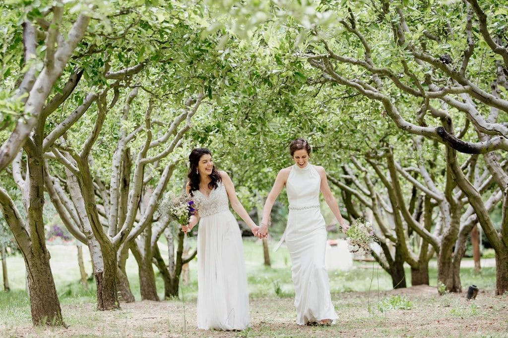 Same sex marriage brides at Nestldown Wedding walking in orchard